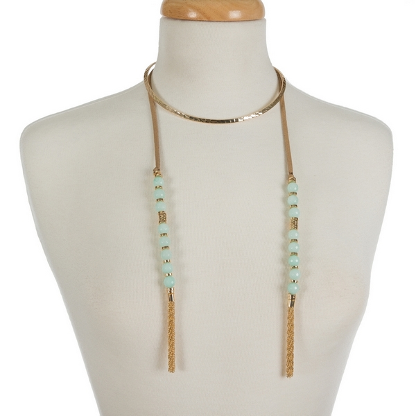 "Gold tone open metal choker featuring tan faux suede pieces with mint green natural stone beads and chain tassels. Approximately 16"" in length."