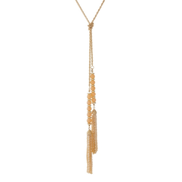 "Gold tone open necklace featuring champagne glass and faceted beads, and tassels on the ends. Necklace can be worn as a wrap necklace or tied as a long tassel necklace. Approximately 50"" in total length."