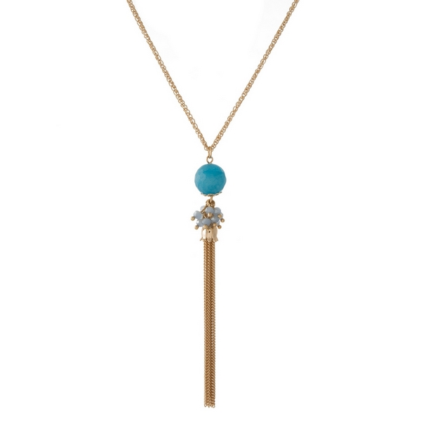 "Gold tone necklace featuring a turquoise natural stone pendant and chain tassel. Approximately 30"" in length."