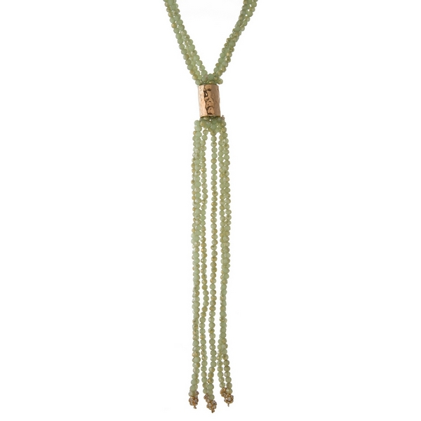 "Light green beaded, multi strand necklace featuring a tassel pendant and gold tone accent. Approximately 26"" in length."