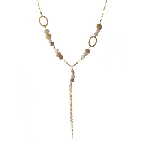 "Gold tone necklace featuring blush and ivory beads and a dainty chain tassel. Approximately 18"" in length."
