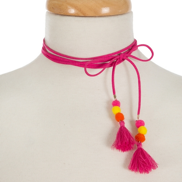 """Hot pink, faux suede wrap necklace featuring yellow and orange pom poms and tassels on the ends. Approximately 60"""" in length."""