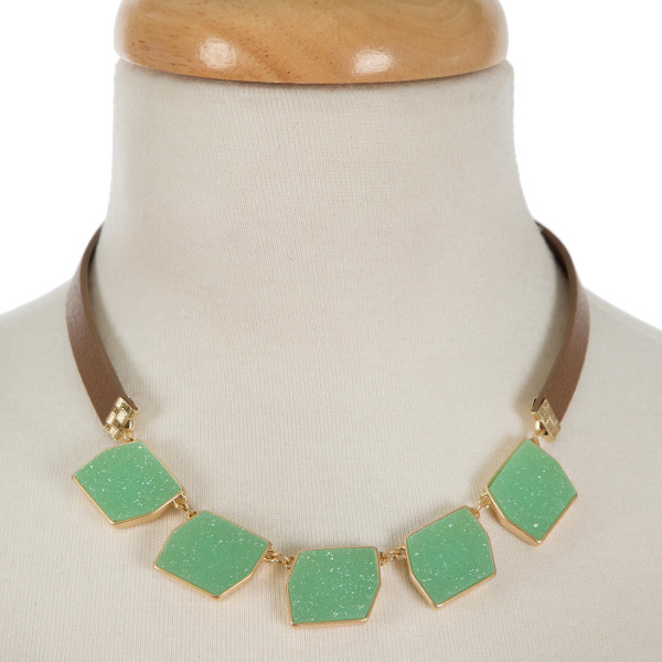 """Brown leather necklace featuring five green faux druzy stones and gold tone accents. Necklace has a snap closure. Approximately 15"""" in length."""