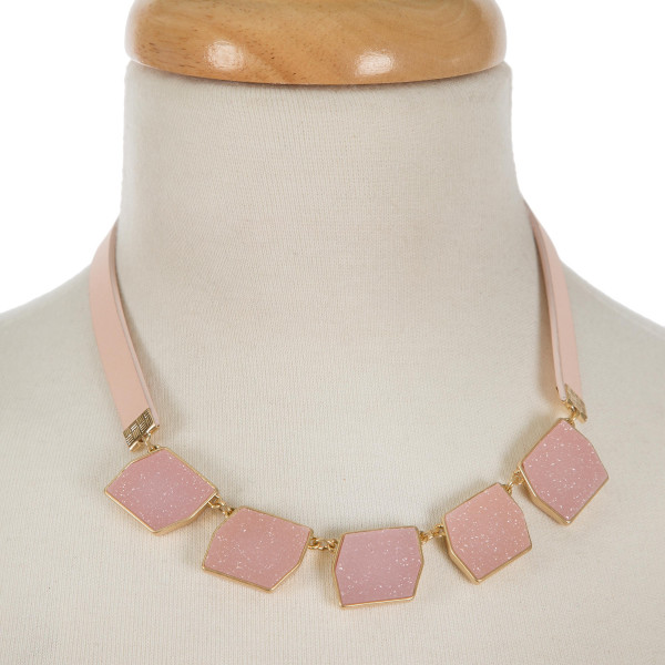 """Pale pink leather necklace featuring five pink faux druzy stones and gold tone accents. Necklace has a snap closure. Approximately 15"""" in length."""