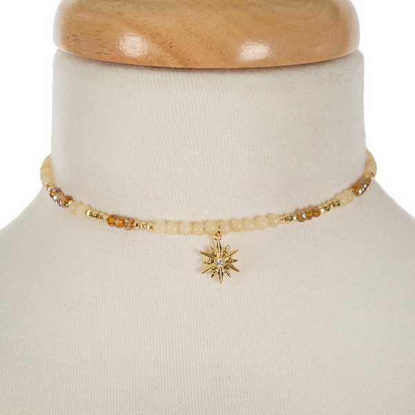 """Gold tone memory wire choker featuring beige and topaz beads and a star pendant. Approximately 5"""" in diameter. Handmade in the USA."""