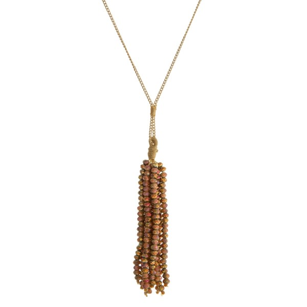 "Dainty gold tone necklace with a brown and gold faceted bead tassel. Approximately 28"" in length."