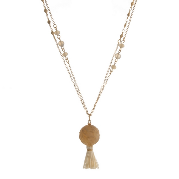 "Gold tone necklace featuring gray faceted beads, a beige bead pendant and an ivory tassel. Approximately 36"" in length."