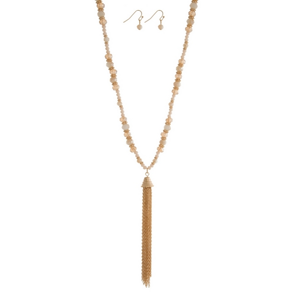 "Gold tone necklace with an ivory beaded chain and a chain tassel pendant. Approximately 27"" in length."