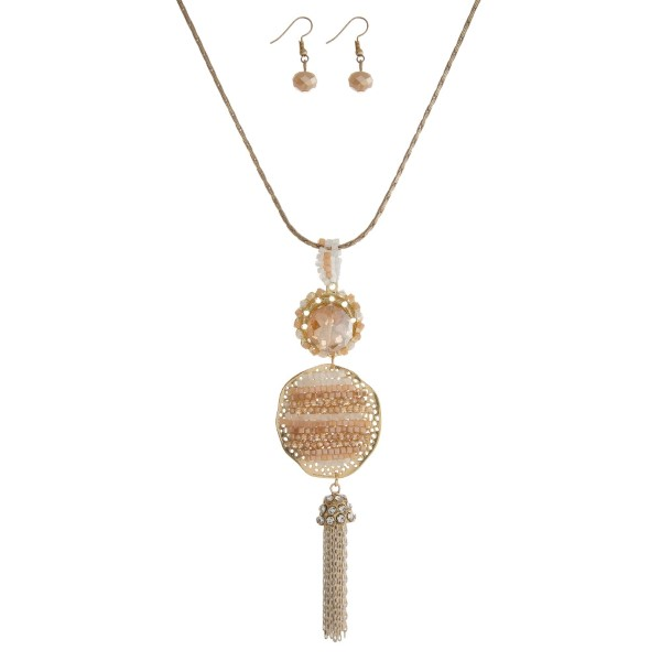 "Gold tone necklace set with a champagne beaded and chain tassel pendant. Approximately 18"" in length."