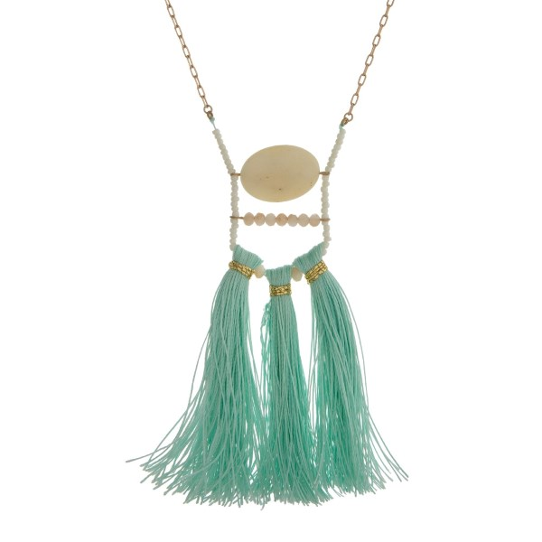 "Gold tone necklace with a beige stone pendant and two mint green tassels. Approximately 30"" in length."