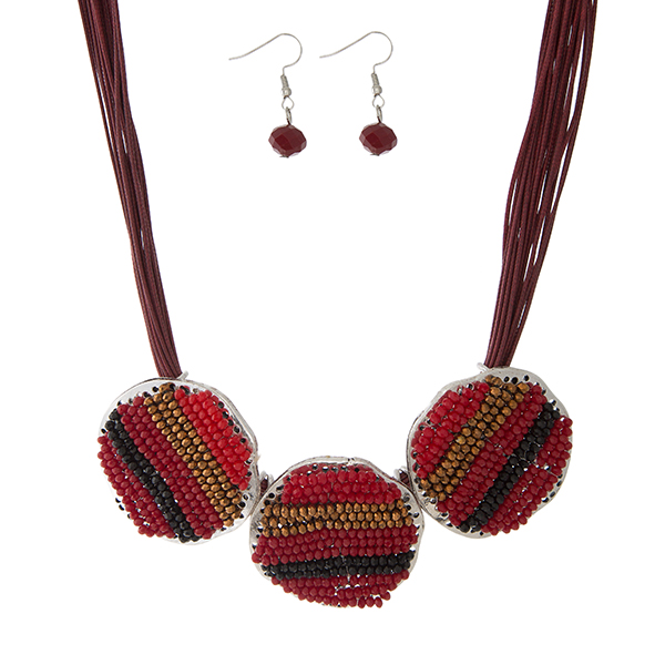 """Burgundy waxed cord necklace set with three red and burgundy beaded circles, and matching fishhook earrings. Approximately 16"""" in length."""