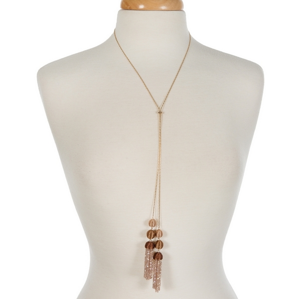 "Gold tone necklace with brown ombre thread wrapped beads and two champagne tassels. Approximately 28"" in length."