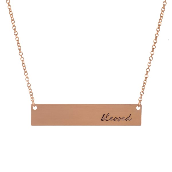 "Dainty rose gold tone necklace with a bar pendant, stamped with ""blessed."" Approximately 16"" in length."
