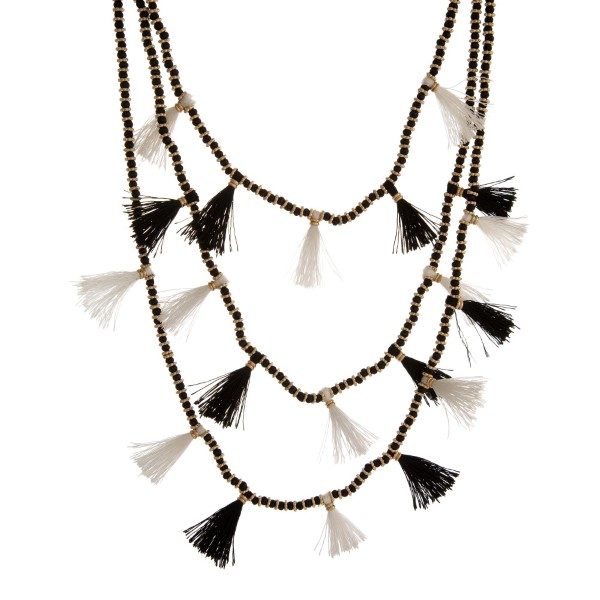 """Three layer, beaded necklace with gold tone accents and thread tassels. Approximately 16"""" to 26"""" in length."""