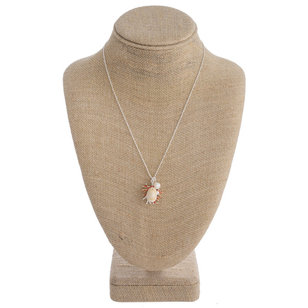 """Long metal necklace featuring a coral detail, puka shell, and pearl accents. Approximately 18"""" in length."""
