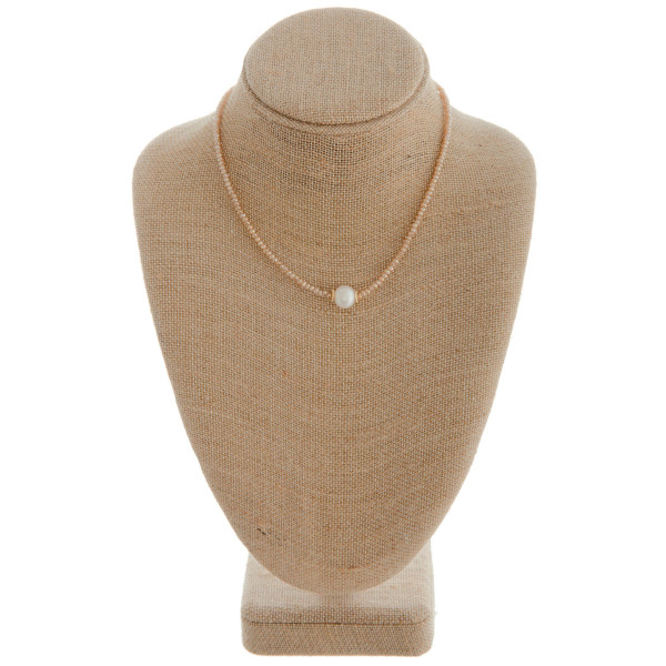 "Short champagne beaded necklace featuring a pearl accent. Measures approximately 16"" in length."