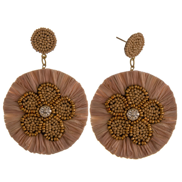 "Circular drop earrings featuring beaded flower details with rhinestone and raffia tassel accents. Approximately 2"" in diameter."