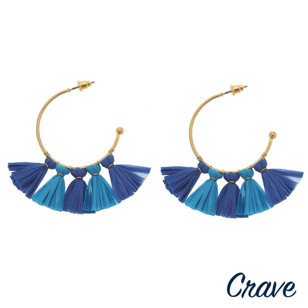 "Gold hoop earrings featuring blue resin tassel accents. Approximately 1.5"" in diameter."