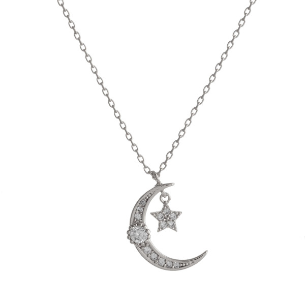 """Dainty silver chain necklace featuring a cubic zirconia adorned crescent pendant and a star accent. Approximately 18"""" in length. Pendant is approximately 1"""" in diameter."""