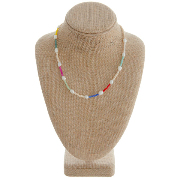 "Necklace featuring wood and glass beads with pearl accents. Measures approximately 18"" in length."