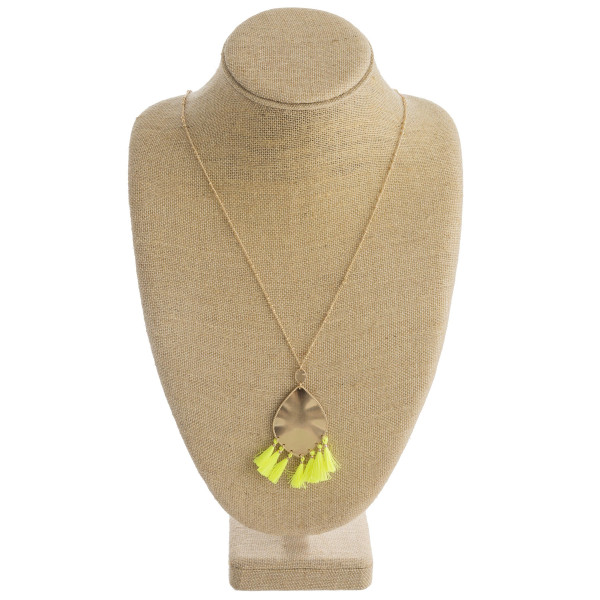 """Long metal necklace featuring a metal plated teardrop pendant with neon tassel details and gold accents. Pendant approximately 3"""". Approximately 36"""" in length overall."""