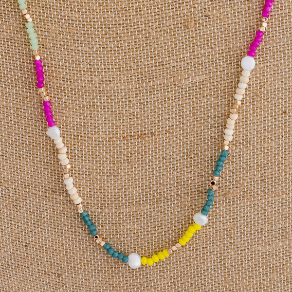 "Long beaded necklace featuring wood and pearl beaded accents. Approximately 30"" in length."