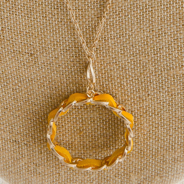 "Dainty cable chain necklace featuring a chain link inspired circular pendant with faux leather woven details. Pendant approximately 1.5"". Approximately 36"" in length overall."
