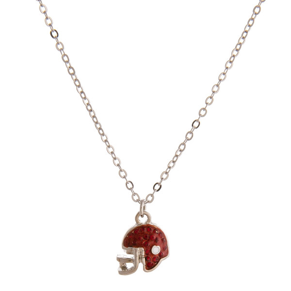 "Dainty cable chain necklace featuring a football helmet with cubic zirconia details. Pendant approximately 1cm. Approximately 18"" in length overall."