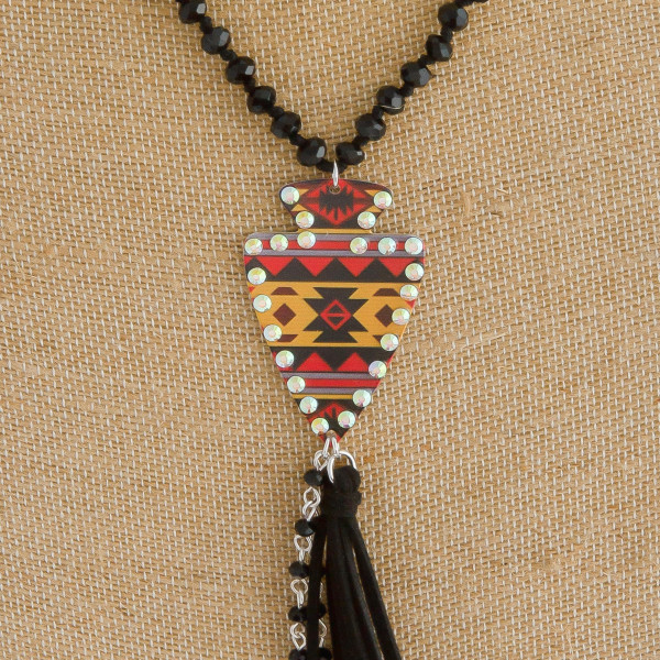 "Long black faceted beaded necklace featuring a metal arrow pendant with western details and a tassel accent. Pendant and tassel approximately 7"". Approximately 42"" in length overall."