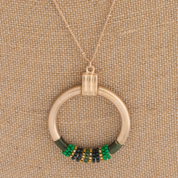 "Long boho necklace featuring a round seed beaded pendant with thread wrapped details. Pendant approximately 2"" in diameter. Approximately 34"" in length overall."