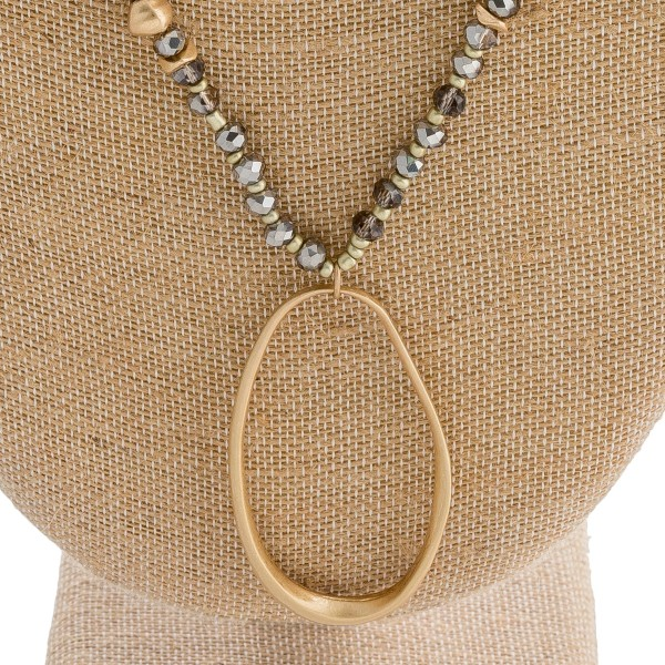 "Long beaded oval pendant necklace with metal accents. Pendant approximately 3"" in length. Approximately 36"" in length overall."