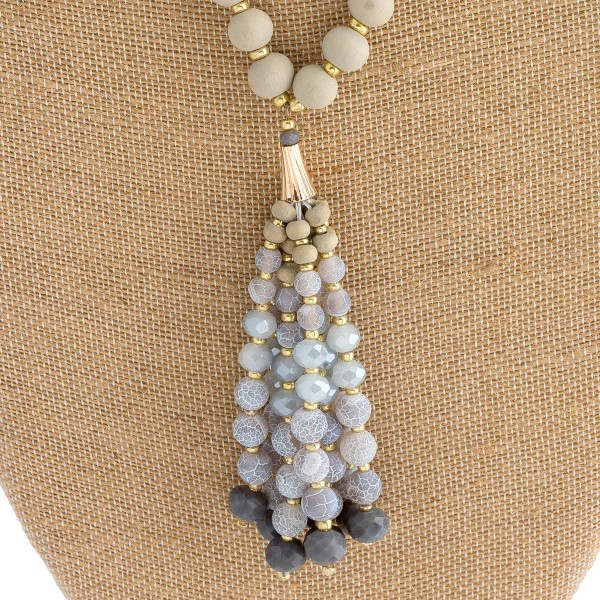 "Long wood beaded necklace featuring natural stone beaded tassel pendant. Pendant approximately 4"" in length. Approximately 38"" in length overall."