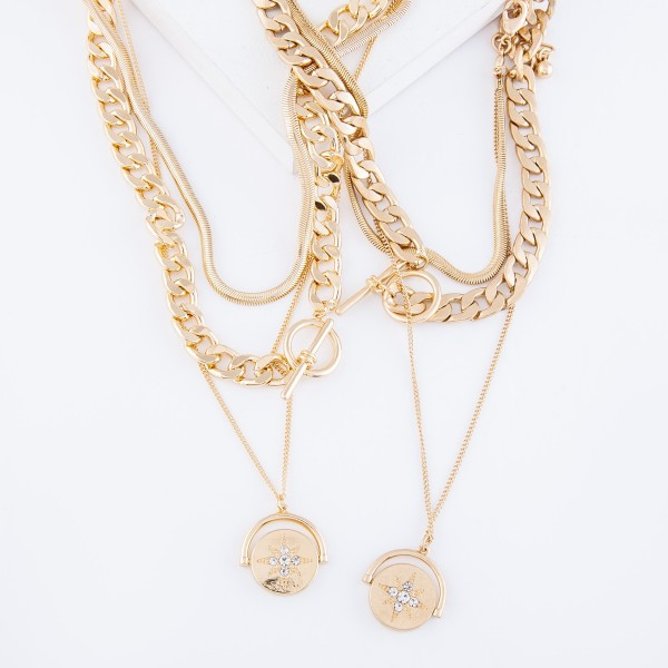 "Curb Chain Link Layered Flip Coin Statement Necklace with Rhinestone North Star Detail in Worn Gold.  - Toggle Bar Clasp  - Detachable Layering Set  - Shortest Layer 16"" L - Approximately 20"" L overall - 2"" Adjustable Extender"