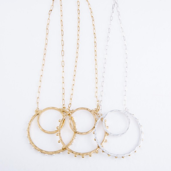 "Long Circular Pendant Necklace Featuring Ivory Pearl Stud Accents in Gold.  - Pendant 2.5""  - Approximately 32"" L - 3"" Adjustable Extender"