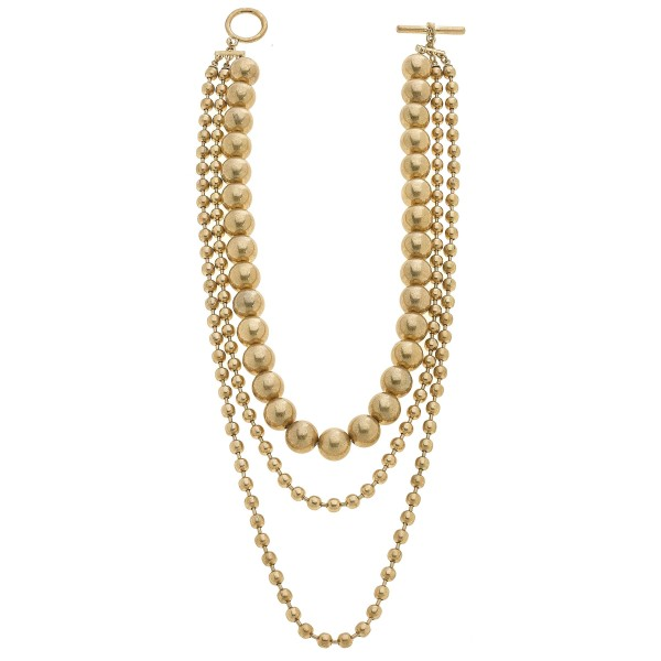 "Ball Chain Beaded Layered Statement Necklace in Worn Gold.  - Bead Sizes: 3mm - 11mm  - Toggle Bar Clasp - Approximately 15"" in Length"