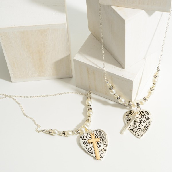 "Short Silver Necklace Featuring Faux Pearl Details, Cross Pendant. and Engraved Heart Pendant that Says ""Love"".   - Approximately 18"" Long"
