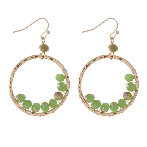 """Gold tone fishhook earrings with a hammered circle shape and wire wrapped light green beads. Approximately 1.25"""" in diameter."""