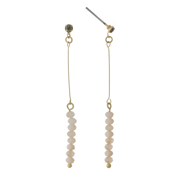 "Dainty gold tone stud earrings featuring ivory faceted beads. Approximately 2"" in length."