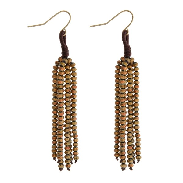 """Gold tone fishhook earrings with a bronze beaded tassel. Approximately 2.5"""" in length."""