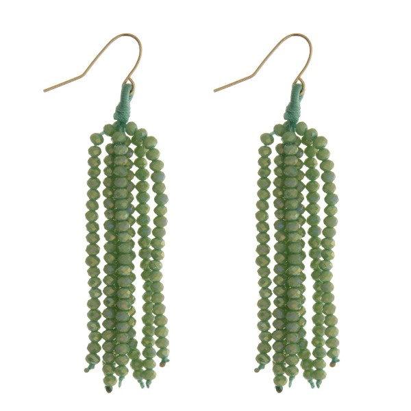 """Gold tone fishhook earrings with a light green beaded tassel. Approximately 2.5"""" in length."""