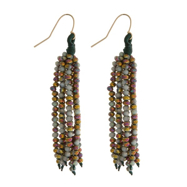 """Gold tone fishhook earrings with a green beaded tassel. Approximately 2.5"""" in length."""