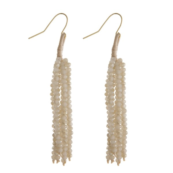 "Gold tone fishhook earrings with an ivory beaded tassel. Approximately 2.5"" in length."