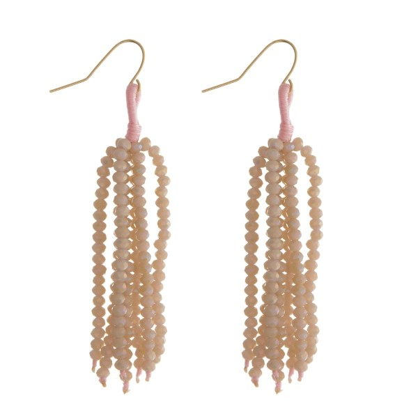 """Gold tone fishhook earrings with a pale pink beaded tassel. Approximately 2.5"""" in length."""