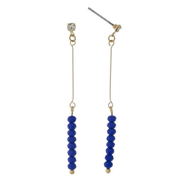 "Dainty gold tone stud earrings featuring royal blue faceted beads. Approximately 2"" in length."