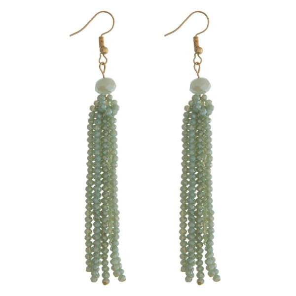 """Gold tone fishhook earrings with a mint green faceted bead tassel. Approximately 3"""" in length."""