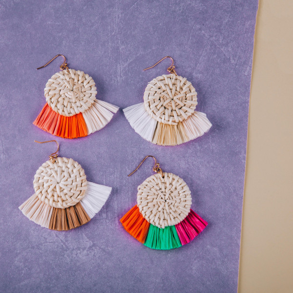 "Woven raffia disc earrings featuring raffia tassel details. Approximately 2"" in length."