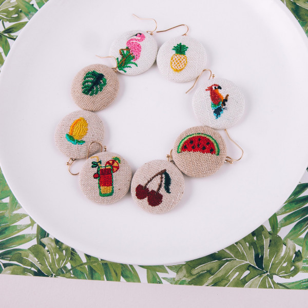 "Fabric circular drop earrings featuring a lemonade embroidered detail. Approximately 1"" in diameter."