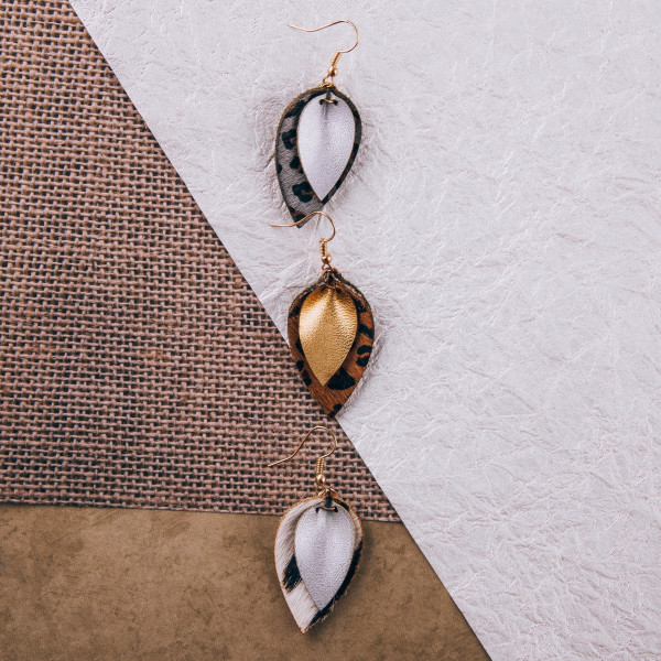 "Genuine leather drop earrings featuring animal print and gold details. Approximately 1.5"" in length."