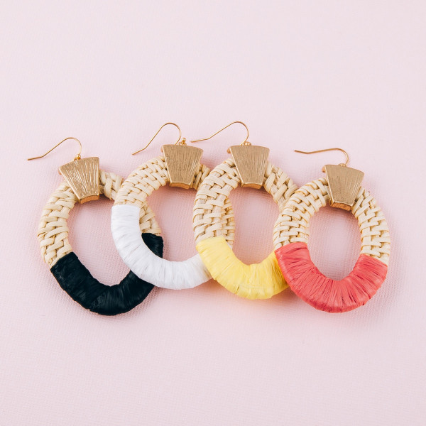 "Large rattan woven earrings featuring raffia wrapped details and a gold accent. Approximately 2"" in length."