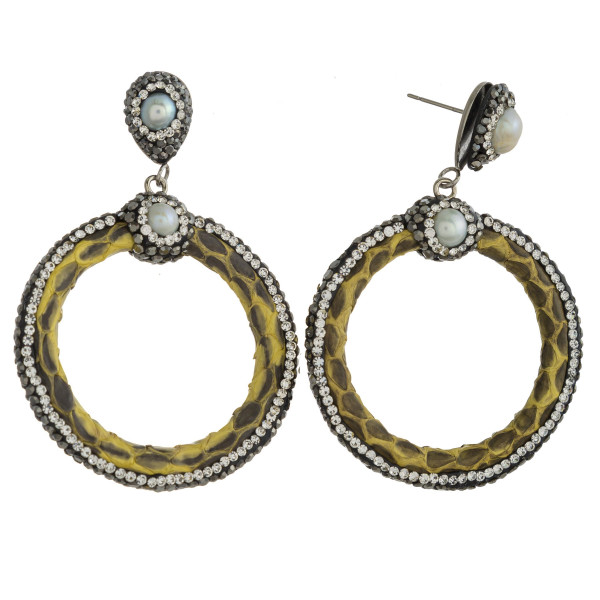 "Circular faux leather earrings featuring rhinestone details and pearl accents with a stud post. Approximately 2.5"" in length."